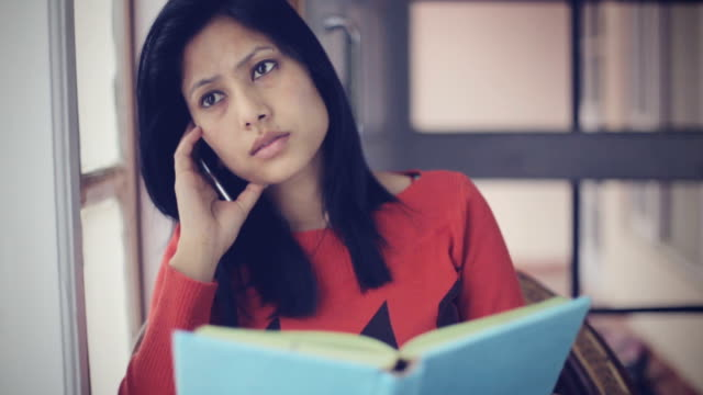 Serene Asian young adult student near window with book.