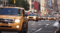 A series of cabs move quickly down 8th Avenue at dusk