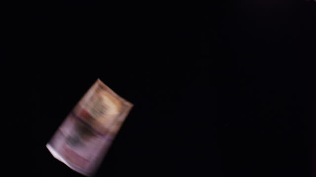 A series of currency and large denominations of paper money (dollar bills) float and flip past camera over a black background.