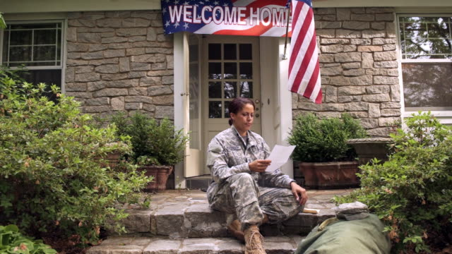 Serious African American soldier reading letter on front stoop