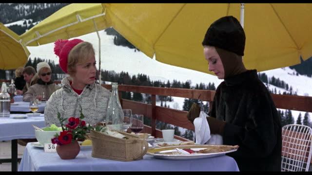 A serious and sad woman (Audrey Hepburn) announces divorce to friend in snowy alpine restaurant