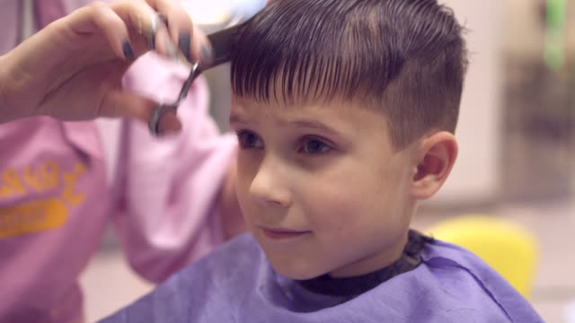 Serious boy sitting in chair in protective apron and getting hair cut by hairdresser