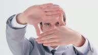 Serious brunette man making a hand gesture