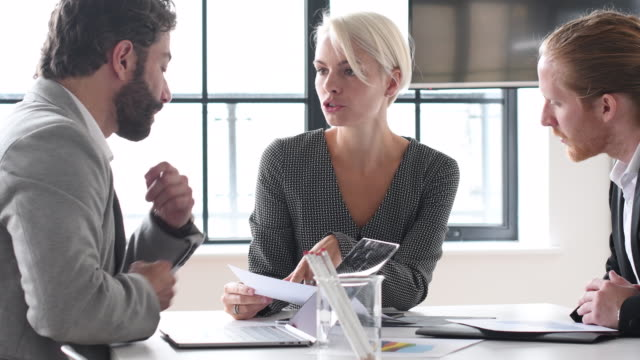 Serious looking female manager explaining to two male colleagues in meeting