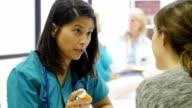Serious nurse talks with patient about a diagnosis