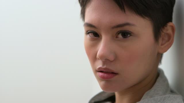 Serious young Asian young woman looking at camera
