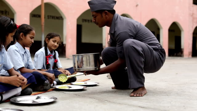 Servant serving midday meal to school students, Haryana, India
