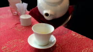 Serve pour tea water to cup