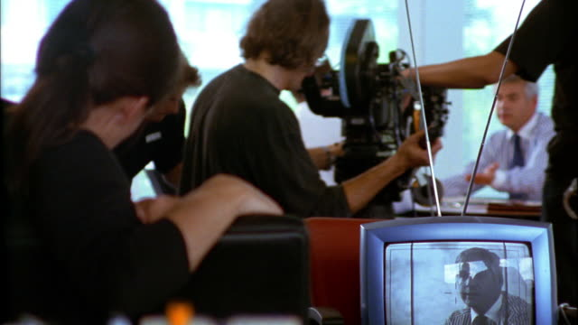 A TV set captures the video that a film crew gets as they move past the actors on a dolly.