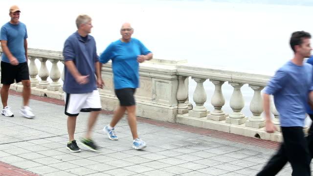 Sieben Männer, die über eine Brücke zu Fuß