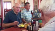 Seven white male senior citizens are eating lunch at a diner in Phoenix Arizona on December 13 Seven white male senior citizens are talking