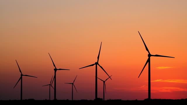 Seven Wind Turbines At Sunset