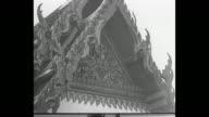 DOWN several domeshaped stupa structures tall spires / MLS man walks between stupas / CU ornate decor above entrance to building / TILT UP novice boy...