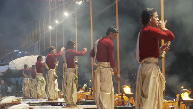 Several men in a line making an incense offering to the Ganges river.