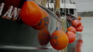Several red buoys hanging from sides of two fishing boats