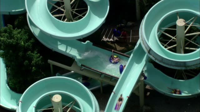 Several swimmers ride on mats down a giant water slide. Available in HD.