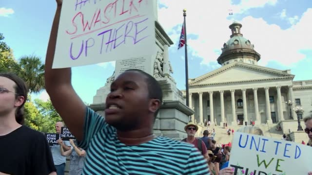 Several thousand protesters gather under the controversial Confederate flag at South Carolinas state legislature demanding it be taken down in...