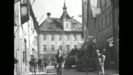 Several views of American GIs walking through small town with tanks halftrack personnel carriers several scenes of town square with fountain with...