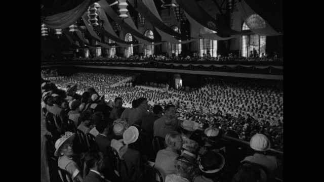 VS several views of Dahlgren Hall with graduating class of US Navy midshipmen seated on floor of Dahlgren Hall audience seated at sides and above /...