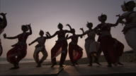 Several young women pose then perform the 'Odissi' dance on the beach while wearing traditional costumes. Available in HD.