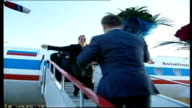 Kadyrov away up steps to aircraft carrying bouquet of flowers as hugs unidentified woman * * FLASH