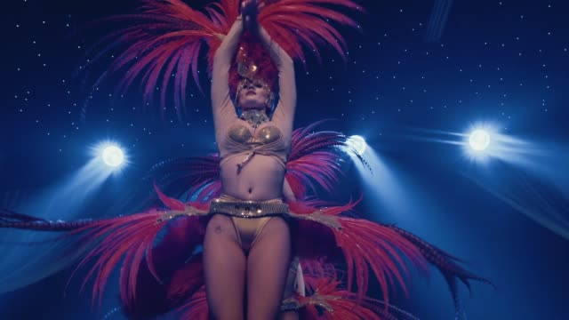 A sexy female burlesque dancer dancing in a skintight outfit with large feathered fans NO