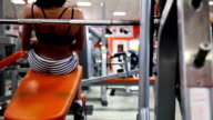 Sexy girl does bench press at fitness center