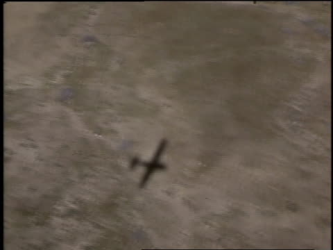 1968 AERIAL Shadow of a small plane flying over desert with an abandoned car in view