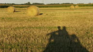 HD: Shadow Of Couple Sitting On Hay Bale