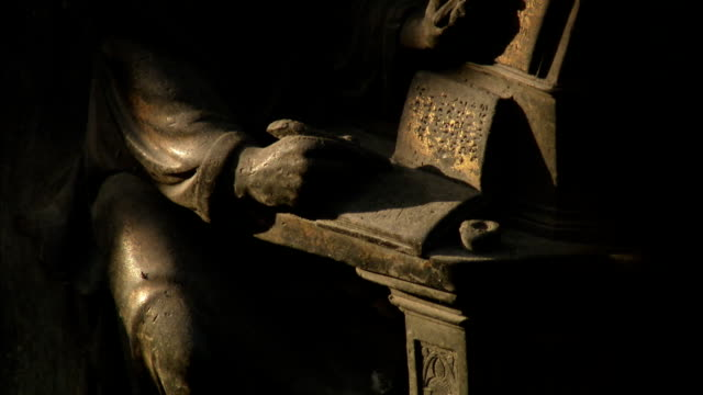 Shadows fall across a bronze statue in Florence, Italy. Available in HD.