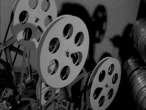 Shadows of film spools turning are cast onto a wall