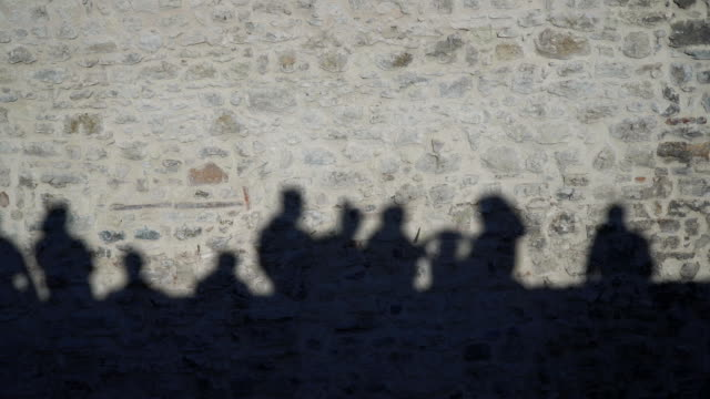 Shadows Of The People On Stone Wall