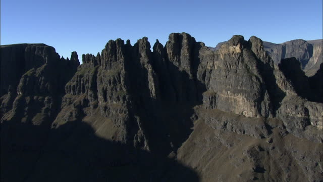 Shadows stretch across the jagged cliffs of the Drakensberg Mountains.
