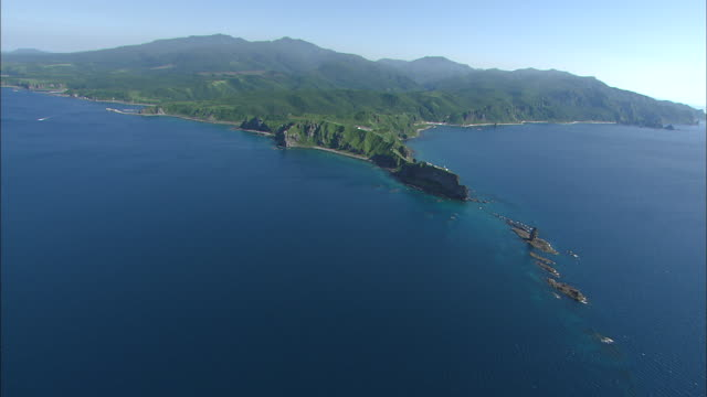 Shakotan's Cape Kamui jutting out into the blue Sea of Japan and reefs of Kamui Rock Wide and Long Aerial Shot