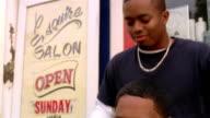 Shaky close up barber brushing man's hair and taking off smock / man standing up / Santa Monica, California