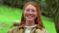 Shaky close up tilt up portrait red-headed teen girl holding lamb and smiling outdoors / California
