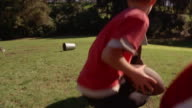 Shaky low angle medium shot boy snapping football to quarterback / boy faking pass and throwing ball