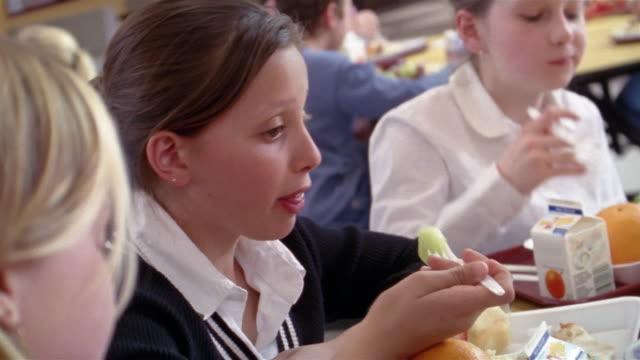Shaky medium shot girls eating in school cafeteria/ Goram, Maine