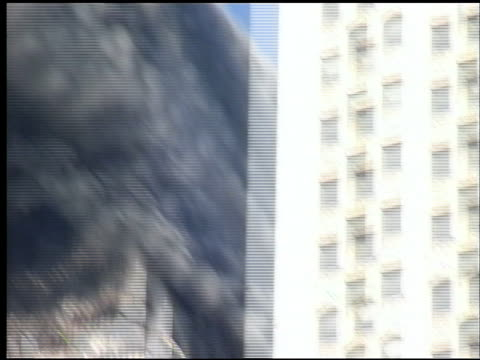 Shaky Pedestrian POV of smoke from WTC behind buildings on Broadway at City Hall Park / Woolworth Building in foreground / crowds mill about police...