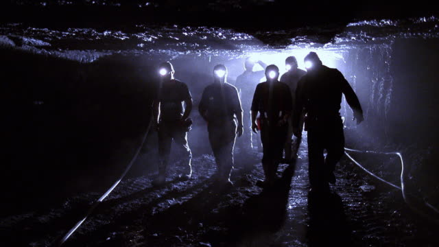 Shaky tracking shot miners with headlamps walking through dark tunnel in mine / Kentucky