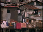 Shanty town stilt houses on river bed rubbish strewn all over the riverbank children play woman cleans clothes in plastic basin Manilla