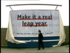 Shares Up Vauxhall Bridge EXT MS Bryan Gould MP unveiling hoarding 'Make It A Real Leap YearNew Year new ideas new government Labour' ITN