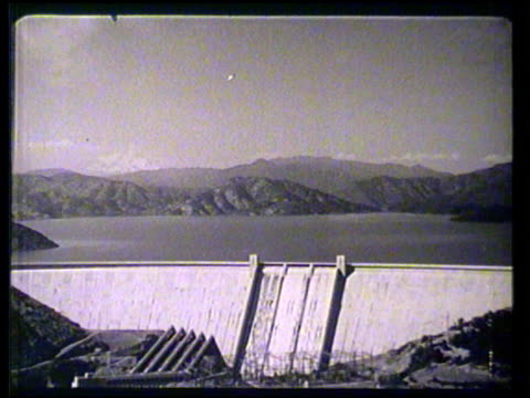 Shasta Dam w/ Shasta Lake mountains BG five penstocks leading to hydroelectric powerhouse FG XHA MS Reservoir water flowing down from open flood...