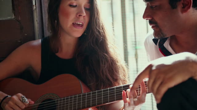 She plays guitar and sing for him