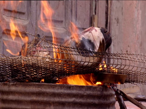 Sheep heads burning on wire mesh above flames Morocco