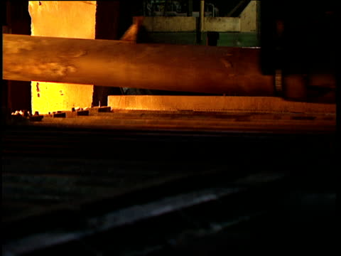 Sheet of red-hot steel being removed from furnace by fork-lift machine placed on roller bed and taken away