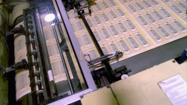 CU, HA, Sheets of American ten dollar bills moving fast on conveyor, Washington DC, USA
