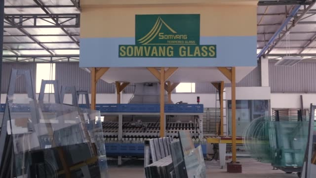 Sheets of glass sit at the Somvang Glass Factory on the outskirts of Vientiane Laos on Wednesday Nov 1 Signage is displayed at the Somvang Glass...
