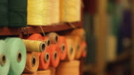 A shelf full of colorful spools of thread