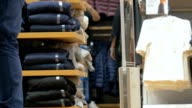 Shelves with clothes in retail store